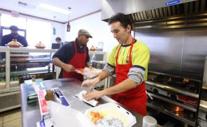 Co-owner Naoufal Bounkhoul, right, and Fahad Khan, center, prepare food at Kabob House in Wards Corner. (Bill Tiernan | The Virginian-Pilot)